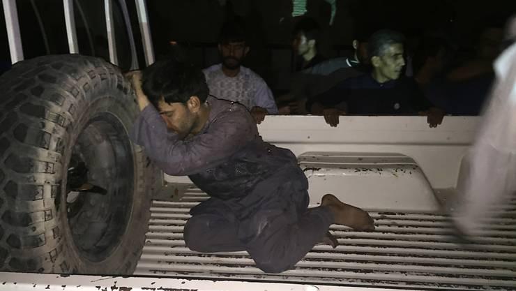Ein verwundeter Mann ruht nach dem Anschlag auf einem Auto.