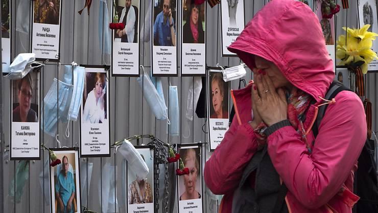 Eine Frau reagiert als sie an einer inoffiziellen Gedenkstätte für St. Petersburger Medizinern vorbeigeht, die während ihrer Arbeit am Coronavirus erkrankt sind und daran gestorben sind. Foto: Dmitri Lovetsky/AP/dpa