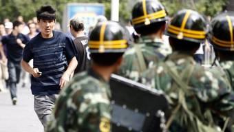 Ein Uigure läuft auf eine Gruppe von chinesischen Sicherheitskräften zu.