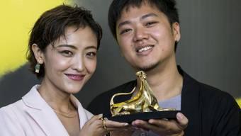 """Die chinesische Schauspielerin Luna Kwok und der singapurische Regisseur Siew Hua Yeo posieren in Locarno mit dem Goldenen Leoparden für den Siegerfilm """"A Land Imagined""""."""