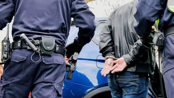 Polizisten nehmen die mutmasslichen Einbrecher fest. (Symbolbild)