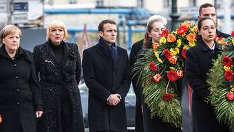 Macron (Mitte) auf dem Weg zur Neuen Wache, der zentralen Gedenkstätte in Deutschland für die Opfer von Krieg und Gewaltherrschaft. Dort legte er unter anderem mit Bundeskanzlerin Merkel (l.) und Bundestagsvizepräsidentin Roth (Grüne, 2. von links) Kränze nieder.