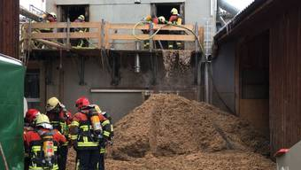 Feuerwehrleute löschen die Glut in den Holzschnitzeln und Holzspänen des Schüpfener Silos.