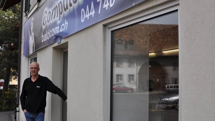 Jürgen Baldensperger vor seinem Geschäft mit dem provisorischen Werbebanner, das er bis an Ostern entfernt haben will.  BHI