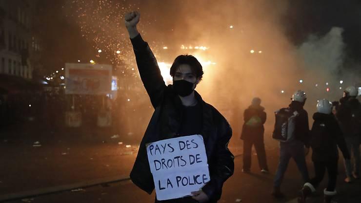 Ein Teilnehmer einer Demonstration hält während eines Protestes gegen ein neues Sicherheitsgesetz ein Schild mit der Aufschrift «Land der Polizeirechte» in der Hand. Foto: Francois Mori/AP/dpa