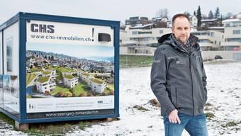 In zwei Jahren werden auf dieser Wiese an der Hinterdorfstrasse acht Häuser stehen. Acht Häuser: Die Visualisierung am Container zeigt die Überbauung, die Christian Schweizer vermarktet.