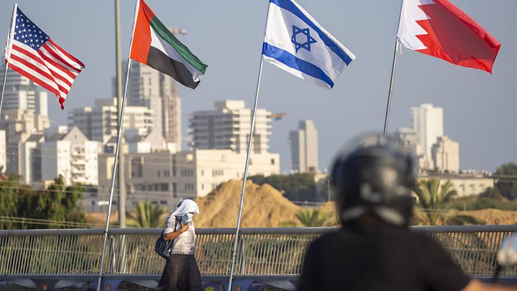Eine Frau geht an den Flaggen der USA, der Vereinigten Arabischen Emirate, Israels und Bahrains vorbei.