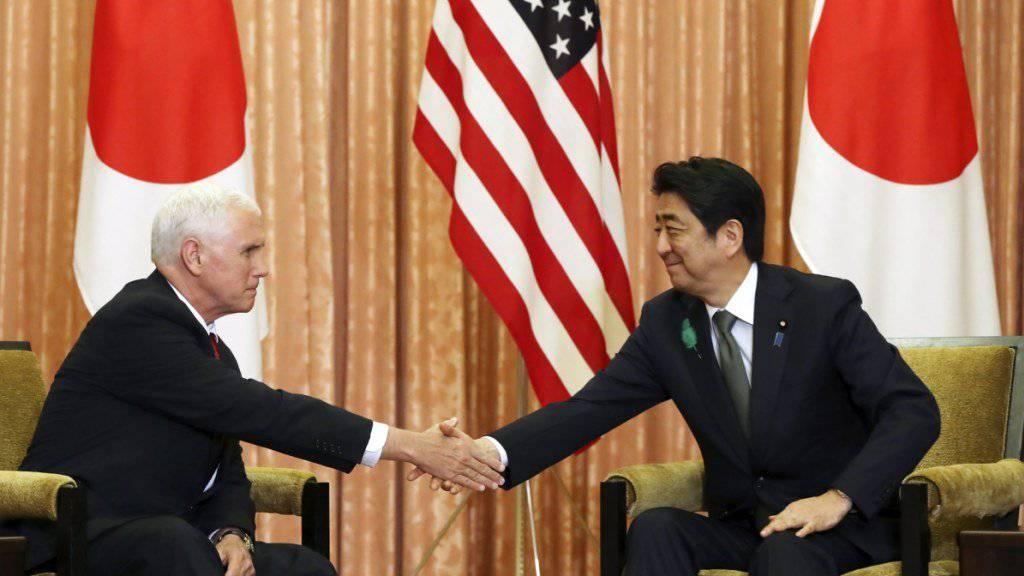 Japans Regierungschef Shinzo Abe (r) und US-Vizepräsident Mike Pence reichen sich die Hand