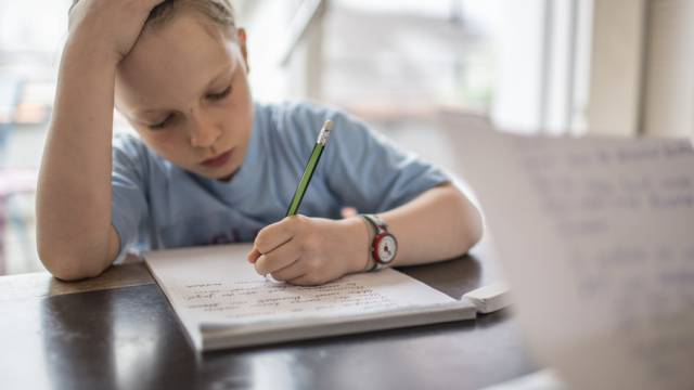 Eine achtjähriges Mädchen übt als Hausaufgabe ein Diktat