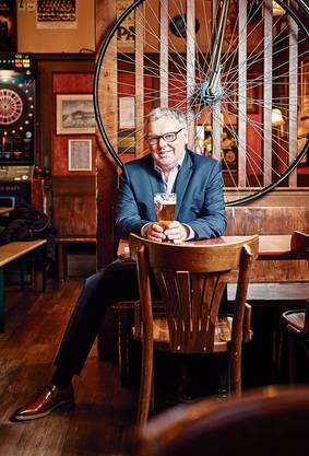 Ian Nicol in seinem Pub. Hinter ihm ein Hochrad, auf Englisch: Penny Farthing.