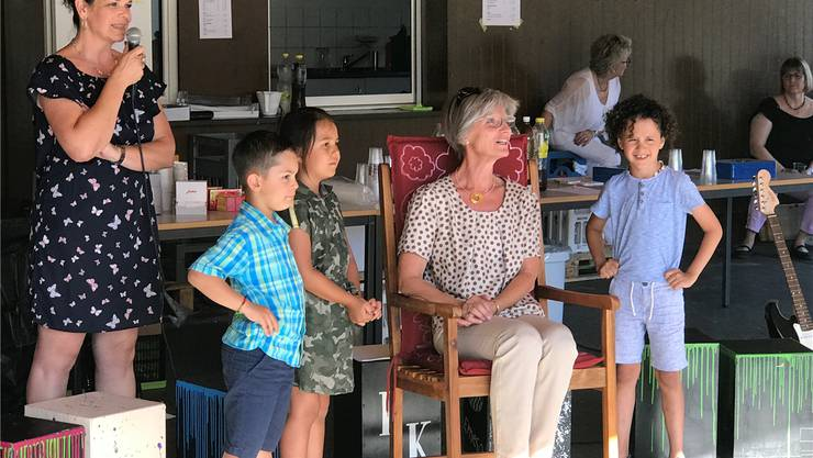 Hanna Ackermann (auf dem Schaukelstuhl) umringt von Kindergartenkindern.