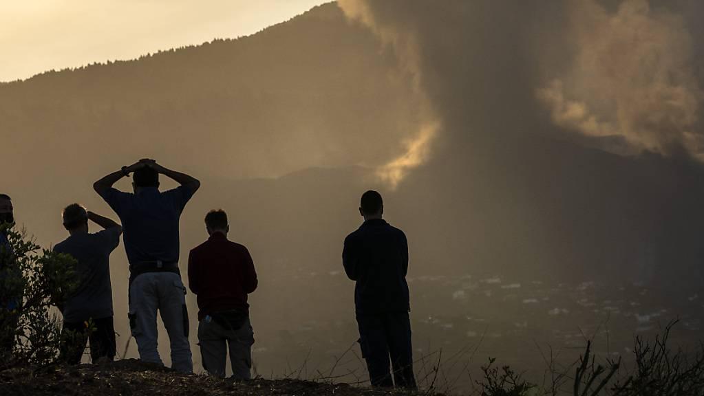 Anwohner blicken von einem Hügel aus auf die Lava, die weiterhin aus einem ausgebrochenen Vulkan auf der Insel La Palma fließt. Foto: Emilio Morenatti/AP/dpa