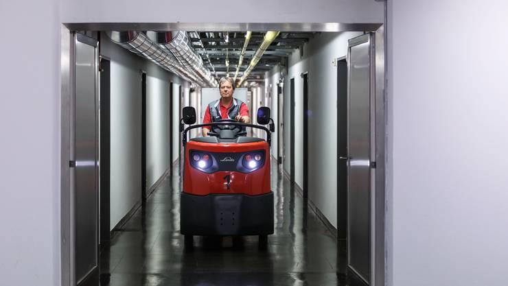 Bruno Strub, Mitarbeiter Technischer Dienst, fährt ein rotes Schleppwägelchen. Mit diesen werden Wäsche oder Mittagessen auf die verschiedenen Stationen der Psychiatrie verteilt.
