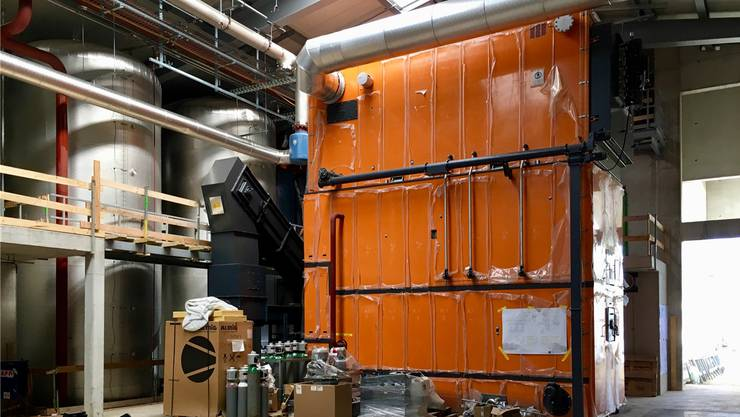 Holzschnitzel-Heizkessel und Heisswasserspeicher (links) in der Heizzentrale.
