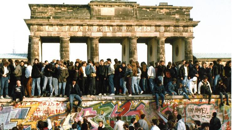 Berliner belagern die Mauer vor dem Brandenburger Tor.