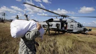 Soldaten der US-Navy verladen Hilfsgüter auf den Philippinen
