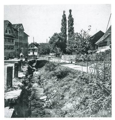 Die Marktstrasse mit dem noch offenen Bach, der 1950 zugedeckt wurde und heute unter dem Trottoir verläuft.