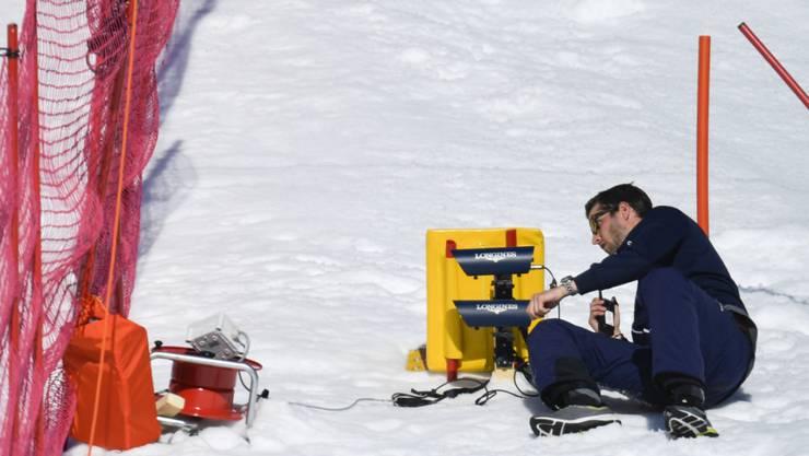 Ein Helfer werkelt in Crans-Montana an einer Zeitmessanlage