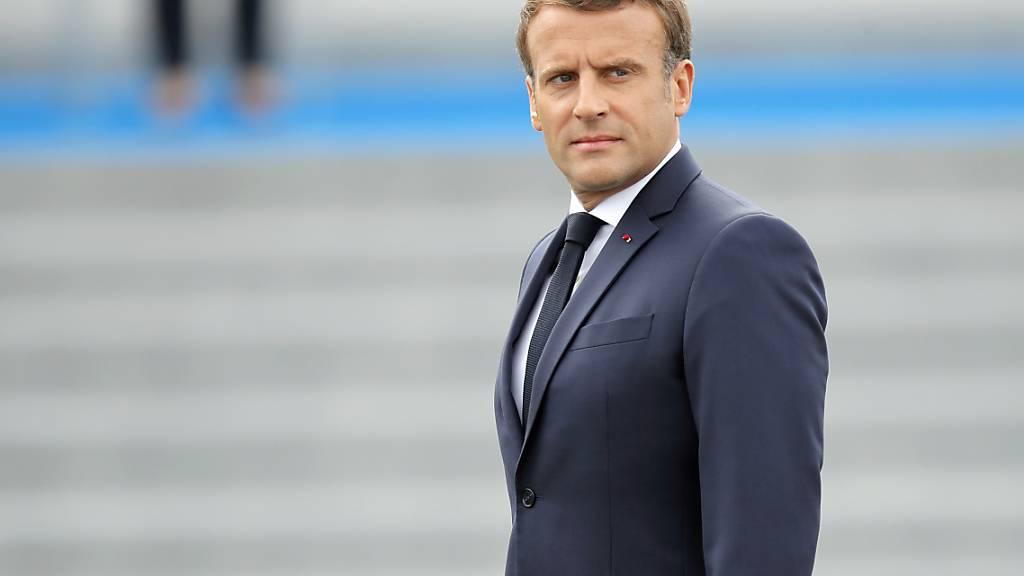 Emmanuel Macron, Präsident von Frankreich, inspiziert Truppen vor der Militär-Feier. Foto: Christophe Ena/AP/dpa