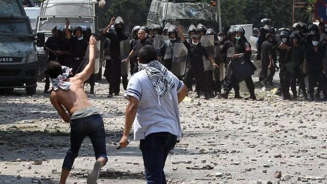 Demonstranten werfen vor der US-Botschaft in Kairo mit Steinen gegen die Polizisten