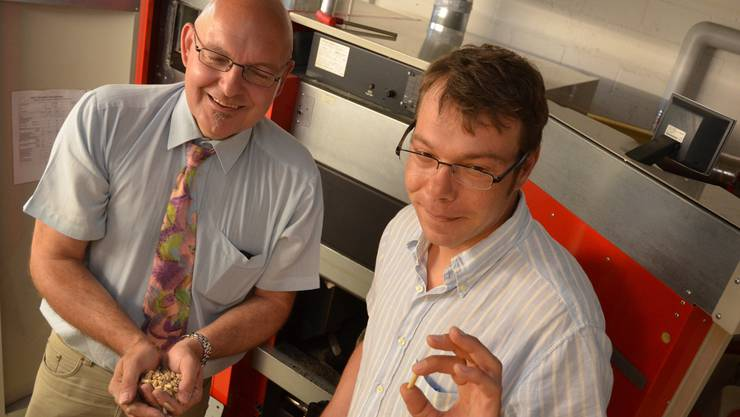 Jules Pikali (links) und Mathias Grimm vom Verein Holzenergie Freiamt machen im Schulhaus Geltwil auf die Vorzüge einer Holzpelletheizung aufmerksam. ES