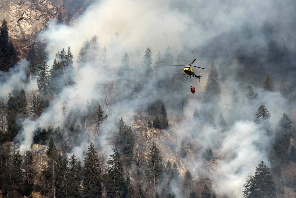 Löschhelikopter versuchen den Waldbrand zu löschen (© Keystone/Ti-Press/Gabriele Putzu)