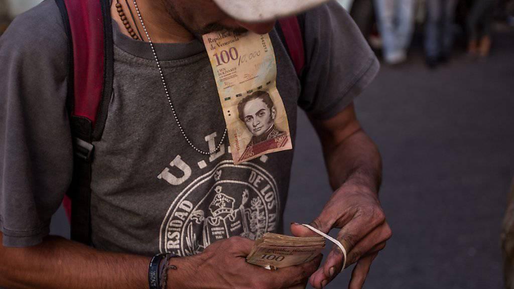 Ein Mann bündelt seine Geldscheine in Caracas.