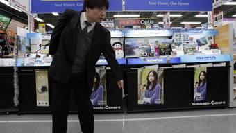 Ein Mann steht in Tokio vor einem Olympus-Stand (Symbolbild)