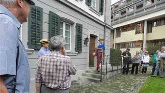Der Lokalhistoriker Heini Stäger (im Hintergrund vor dem Emanuel-Isler-Haus)erfreute die Dorfwanderer mit seinen Storys von früher.
