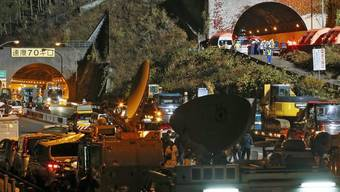 Schweres Rettungsgerät und Übertragungswagen von Fernsehsendern stauen sich vor dem Sasago-Tunnel in Japan