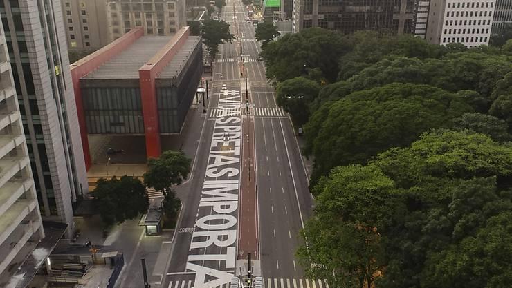 """Der Schriftzug """"Black Lives Matter"""" in portugiesischer Sprache ist auf einer Straße von Sao Paulo zu lesen. Foto: Andre Penner/AP/dpa"""