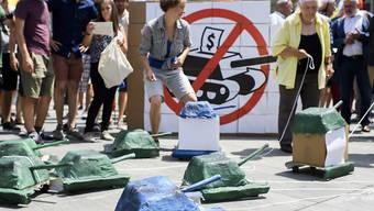 Auf kleinen Papp-Panzern werden die Unterschriften der Initiative für ein Verbot von Kriegsgeschäften zur Bundekanzlei gebracht.