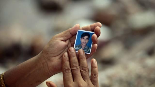 Eine Frau hält ein Foto eines Vermissten (Archiv)