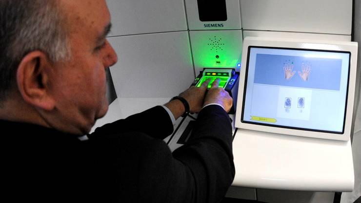 Gewusst wie: Regierungsrat Hans Hollenstein demonstrierte Ende Januar die Geräte und Abläufe zur Erfassung von Gesichtsbild und Fingerabdrücken für den neuen Pass. (EQ Images)