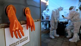 dpatopbilder - Ein Paar orangefarbener Schutzhandschuhe hängt aus einer Testkabine, während Mitarbeiter des Gesundheitswesens sich auf den Tag in einem COVID-19-Testzentrum des nordöstlichen indischen Bundesstaates Nagaland vorbereiten. Foto: Yirmiyan Arthur/AP/dpa