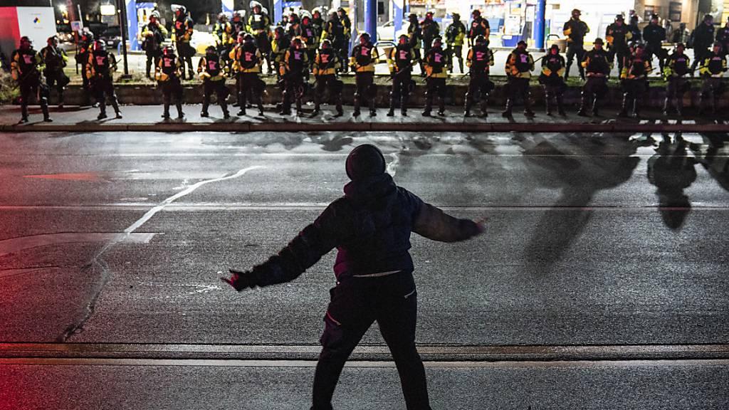 Ein Demonstrant steht während eines Protests gegen Polizeigewalt vor Polizisten. Knapp elf Monate nach dem Tod von George Floyd in Minnesota ist im selben US-Bundesstaat erneut ein Schwarzer von der Polizei getötet worden. Foto: John Minchillo/AP/dpa