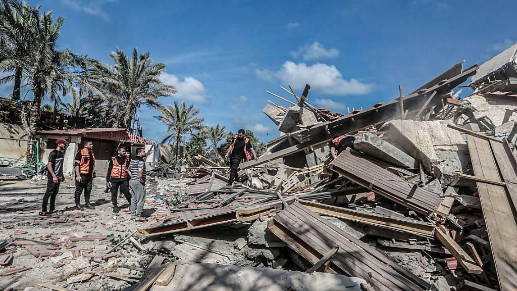 Mitglieder der palästinensischen Zivilverteidigung inspizieren ein eingestürzte Wohnhaus, das am frühen Morgen bei einem israelischen Luftangriff zerstört worden ist. Foto: Mohammed Talatene/dpa