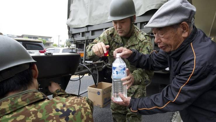 Sicherheitskräfte verteilen Wasser an Erdbebenopfer in der Stadt Mashiki in der Provinz Kumamoto. In den Notaufnahmelagern herrscht nach der Erdbebenserie in Japan mit mindestens 42 Toten weiter Mangel an Lebensmitteln.