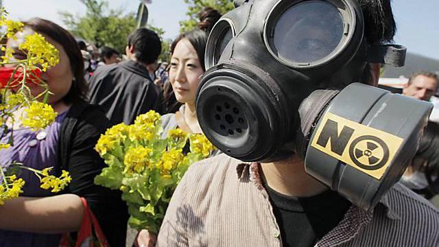 Japaner demonstrieren in Tokio mit Gasmasken und Blumen gegen Atomkraft