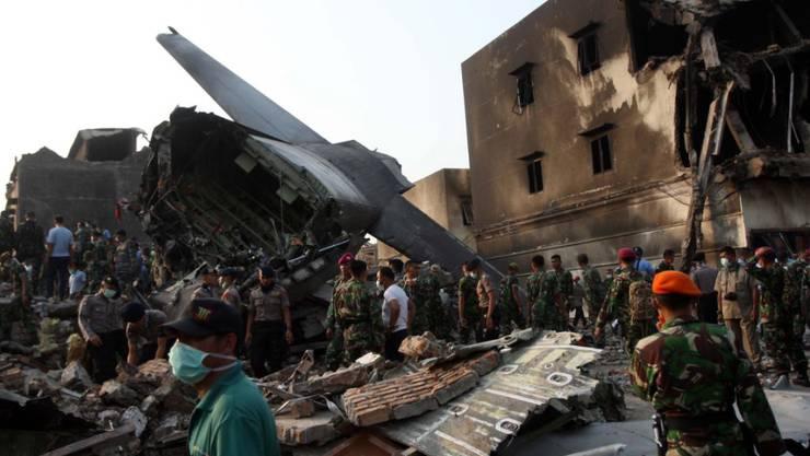 Rettungskräfte suchen in den Trümmern nach Überlebenden des Flugzeugabsturzes. Eine Militärmaschine war in ein Wohngebiet abgestürzt.