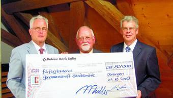 Übergabe: André Schwaller, Präsident der Genossenschaft Schälismühle, flankiert von Alois Müller (links) und Peter Walser von der Baloise Bank SoBa. (Bild: Urs Amacher)