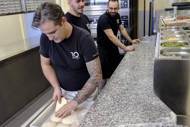 Filialleiter Gezim Murtesi packt den selbst gemachten Teig aus.