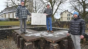 Im ehemaligen Warmluftraum halten Franz Xaver Schenker (links) und Gemeindepräsident Daniel Cartier (Mitte) die alte Info-Tafel, die Fabio Tortoli (rechts) bald neu erstellen wird.