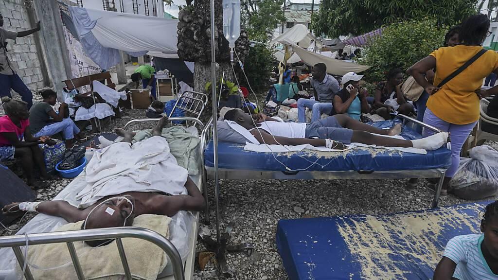 Verletzte liegen in Betten vor dem Krankenhaus Immaculée Conception in Les Cayes, zwei Tage nach einem Erdbeben der Stärke 7,2 im Südwesten des Landes. Nach dem Erdbeben in Haiti ist die Zahl der bestätigten Todesopfer auf 1419 gestiegen. Foto: Fernando Llano/AP/dpa