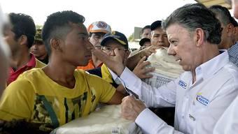 Kolumbiens Präsident Juan Manuel Santos spricht an der abgeriegelten Grenze zu Venezuela mit einem abgeschobenen Mann