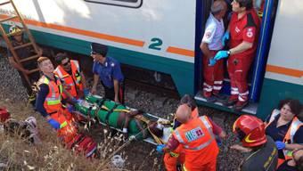 Rettungskräfte helfen einer Frau, die bei einer Zugkollision in Süditalien verletzt wurde.