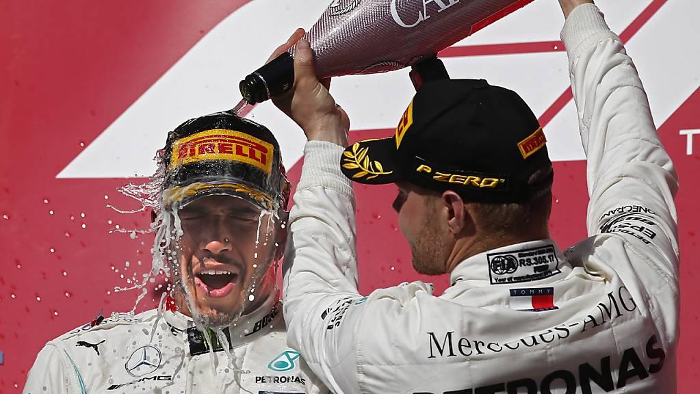 Eine verdiente Dusche für den neuen und alten Weltmeister (links) von Teamkollege Valtteri Bottas.