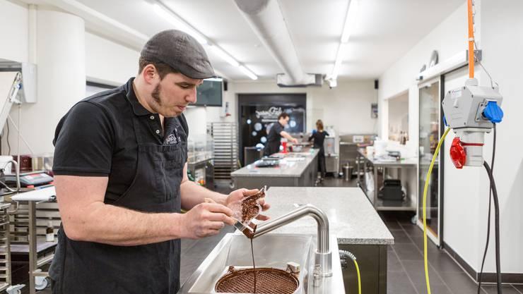 Chocolatier Fabian Rimann fertigt in Wettingen Osterhasen von Hand an. Hier pinselt er die Form aus. Damit der Hase schöner glänzt.