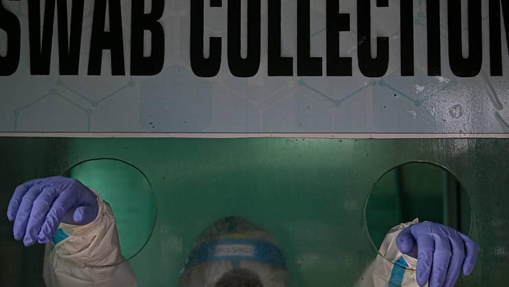 Medizinisches Personal wartet im indischen Gauhati auf eine Probe, für einen Corona-Test. Foto: Anupam Nath/AP/dpa