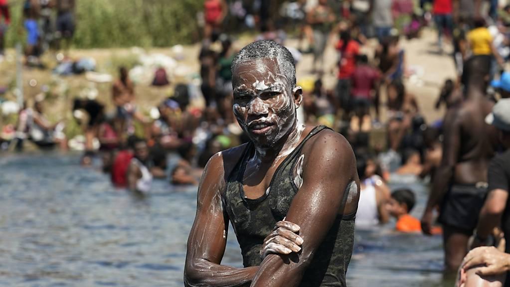 Ein haitianischer Migrant badet im Rio Grande nahe eines Dammes, an dem Migranten von Mexiko in die Vereinigten Staaten ein- und ausreisen. In der US-Grenzstadt Del Rio hat sich die Situation dramatisch zugespitzt. Dort harren Tausende Migranten unter einer Brücke aus. Foto: Eric Gay/AP/dpa